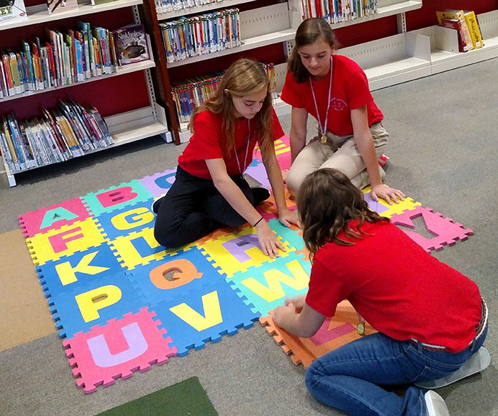 Teens working on a floor puzzle.